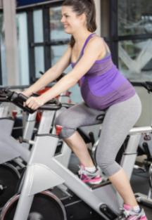 Femme enceinte sur un vélo stationnaire