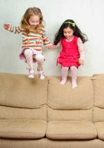 two little girls jumping on sofa